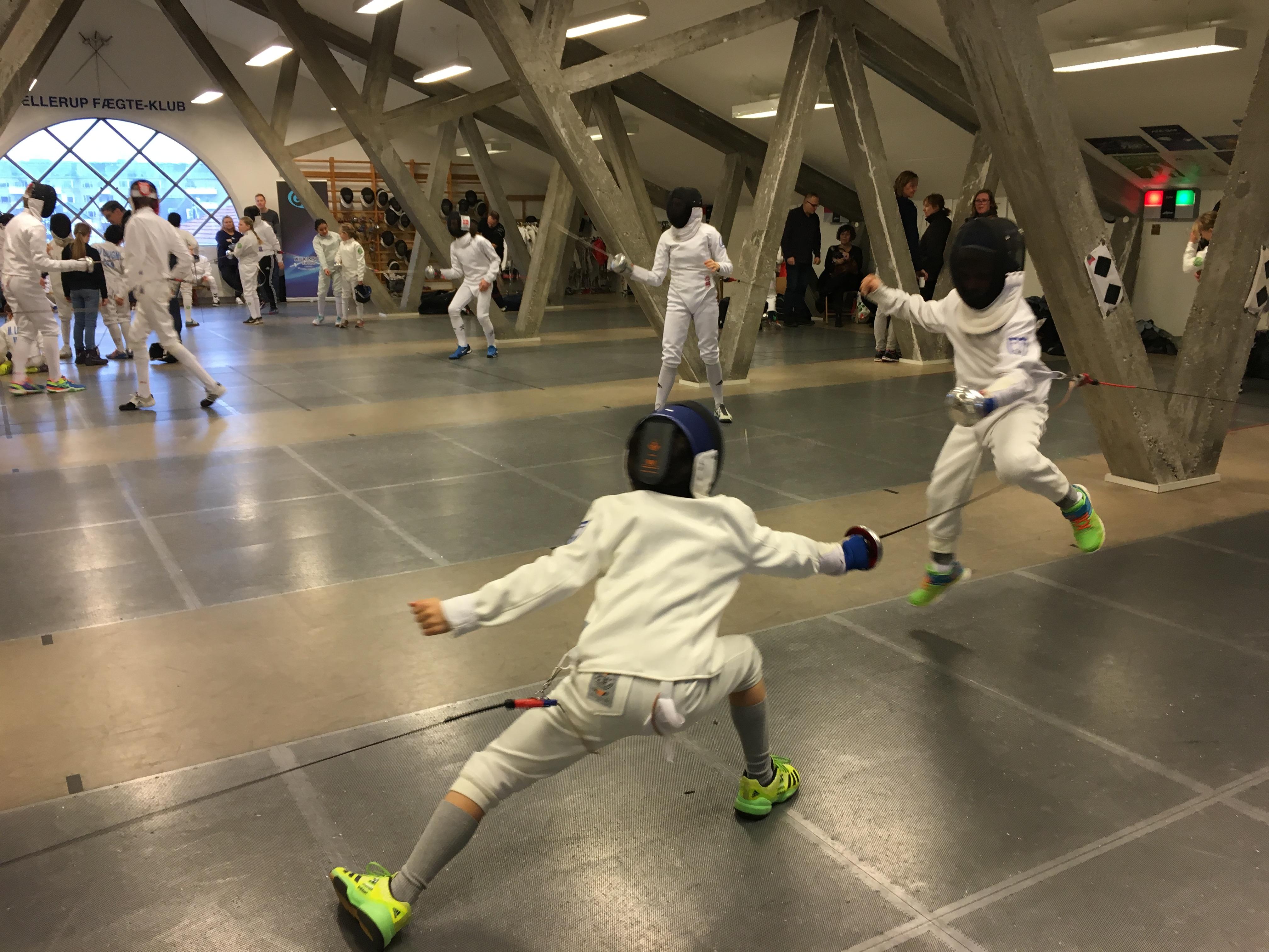 Fægtning. I forggrunden to 9-årige i kamp, hvoraf den ene hopper fremad.