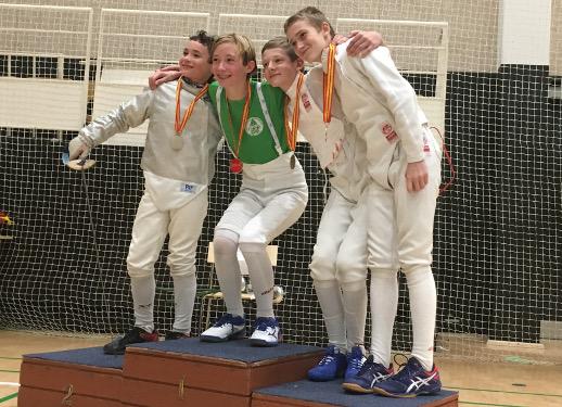 Unge kårdefægtere posserer med medaljer på podie - den ene i sabeludstyr.