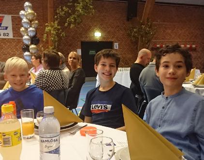 Opdækning til festmåltid i idrætshal. Tre smilende drenge er klar.