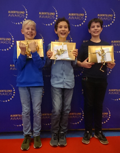 Tre drenge poserer foran væg med logo for Albertslund Awards, holdende en lille pakke hver.