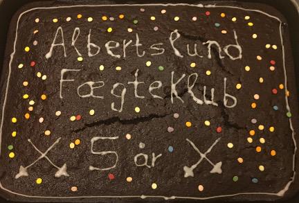 Chokoladekage med teksten: Albertslund Fægteklub 5 år